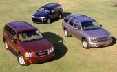 Den röda bilen till vänster är GMC Envoy, till höger har vi Chevrolet TrailBlazer i silvermetallic och lite skyggt i bakgrunden Oldsmobile Bravada i mörkblått.