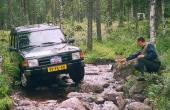 En representant för holländska offroadklubben Kangeroe 4x4 forcerar en stenig bäck i Arvidsjaur med sin Land Rover Discovery och får en fingervisning av co-piloten.