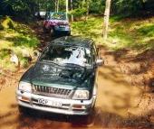 En fyrhjulsdriven Mitsubishi L200 smyger fram i den leriga bokskogsravinen i Hässleholm 1999. Touren vänder sig till både nybörjare och erfarna 4x4-förare, bruksbilar och ombyggda fordon.