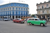 Till höger ett fallfärdigt hus och till vänster ett tjusigt nyrenoverat. Sannolikt ett hotell med en massa flaggor på taket. Passerar gör en grön 1951 Chevrolet Station Wagon med en 1953 Buick i kölvattnet. Moderna bussar flockas runt den blå byggnaden, vilket stärker sannolikheten för att det är ett hotell.