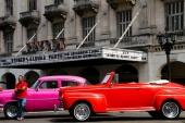 En gammal ärevördig biograf — eller är det en teater? Den rosa är i vart fall en Chevrolet och den röda naturligtvis en Ford från 1946-1948.