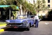 En tjusig 1959 Buick Convertible med distingerad förare. Entrén till ett hotell eller kanske restaurang.