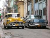 Givetvis omlackerad 1953 Chevrolet medan den parkerade Chevrolet 58:an ser ut att ha kvar originallacken. Smal gata med ruffiga hus medan ett modernt höghus skymtar längre bort.
