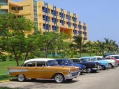 En otroligt fin 1957 Chevrolet, därefter någon småsak och en 1954 Ford. Därefter ett par Chevrolet igen. Notera den moderna hyresfastigheten. Snyggare än många motsvarande i Sverige!