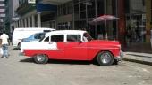 """Som alla ser är det en 1955 Chevrolet Bel Air, men visst har den väl större framhjul än bakhjul? Våldsamt tonade fönster i varje fall. I bakgrunden ett par moderna """"tingestar""""."""