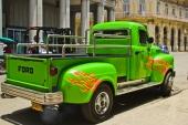 """Här kör vi så det brinner! En elakt grön Ford Pickup med rejäl V8 får man hoppas! Varför skall man annars ha fyra avgaspipor! Snyggt med kromad och riktigt kraftig bakre stötfångare. Storleken på fordonet ger vid handen, att det är en före detta lastbil och blivit en """"Pickup Gigante""""."""
