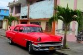 En vansinnigt röd 1955 Mercury framför en nedgången fastighet, som en gång varit kanske lika färgstark som bilen. Mer uppfräschat ser det blå huset ut att vara till vänster i bild.