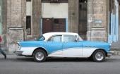 1955 Buick Special 4dr Sedan, snyggt parkerad framför nedsliten fastighet.