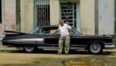 En imponerande 1959 Cadillac Fleetwood Sixty Special framför ett illa nedgånget hus.