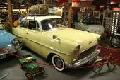 """Längst till vänster skymtar en 1961 Ford Anglia 106E. Modellen som hade """"felvänd"""" bakruta. Den gula bilen är en 1957 Opel Rekord och till höger skymtar bakpartiet av muséets 1956 Lloyd LP400S. Glöm inte att beskåda den otroliga lilla lastbilen med ratt och styrning, som en lycklig gosse en gång i tiden kunde framföra, genom att promenera bakom fordonet!"""