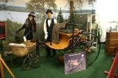 """En autentisk kopia av 1886 Benz Motorwagen, världens första bil. Historien låter berätta att Karl Benz var nöjd över konstruktionen och skulle testköra dagen efter. Men då var bilen borta! Det finns (och har tydligen alltid funnits) """"förvetna"""" kvinnor. Fru Benz hade snott bilen utan makens vetskap och företagit en längre tur!"""